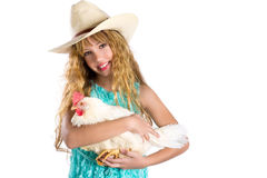 Blond kid girl farmer holding white hen on arms Royalty Free Stock Photography