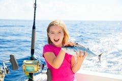 Blond kid girl fishing tuna bonito sarda fish happy catch. Blond kid girl fishing tuna bonito sarda fish happy with trolling catch on boat deck Royalty Free Stock Photography