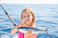 Blond kid girl fishing tuna little tunny happy with catch royalty free stock image