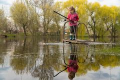 Blond kid girl fishing tuna little tunny happy with trolling catch on boat deck royalty free stock photography