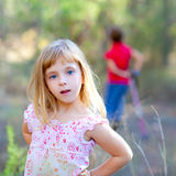 Blond kid girl in forest park. Posing to camera royalty free stock photography