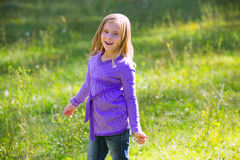 Blond kid girl happy in outdoor green meadow Stock Photography