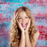 Blond kid girl happy smiling expression hands in face Stock Photos