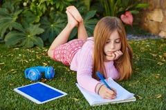 Blond kid girl homework lying on grass turf Stock Photos