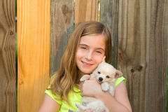 Blond kid girl hug a puppy dog chihuahua on wood Royalty Free Stock Photos