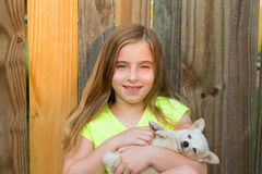 Blond kid girl hug a puppy dog chihuahua on wood Royalty Free Stock Photography