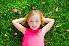 Blond kid girl lying on garden grass smiling aerial view Royalty Free Stock Photo
