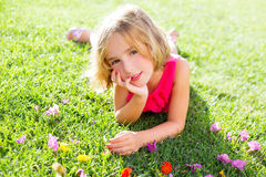 Blond kid girl lying relaxed in garden grass with flowers Stock Photos