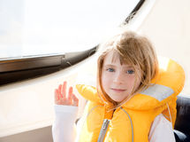 Blond kid girl with marine yellow lifesaver jacket Stock Images