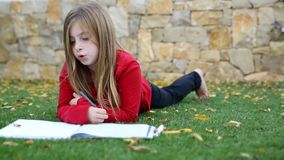 Blond kid girl maths homework laying on grass counting with fingers writing stock video