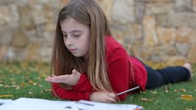Blond kid girl maths homework laying on grass counting with fingers writing stock footage