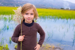 Blond kid girl outdoor holding spike in wetlands lake Royalty Free Stock Photo