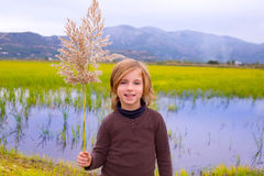 Blond kid girl outdoor holding spike in wetlands lake Stock Photography