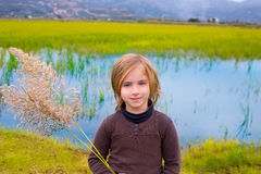 Blond kid girl outdoor holding spike in wetlands lake Stock Images