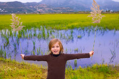 Blond kid girl outdoor holding spike in wetlands lake Royalty Free Stock Image