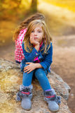 Blond kid girl pensive bored in the forest outdoor. Blond kid girl pensive bored expression in the forest outdoor sitting on a rock royalty free stock photo