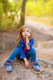 Blond kid girl pensive bored in the forest outdoor. Blond kid girl pensive bored expression in the forest outdoor sitting on a rock Royalty Free Stock Images