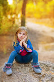 Blond kid girl pensive in the forest stock photos