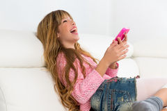 Blond kid girl playing fun with mobile phone on white sofa Stock Photography