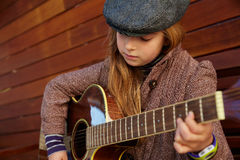 Blond kid girl playing guitar with winter beret Royalty Free Stock Images