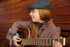 Blond kid girl playing guitar with winter beret Royalty Free Stock Photos