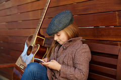 Blond kid girl playing guitar with winter beret Stock Images