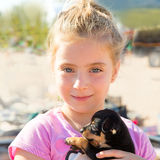 Blond kid girl playing with puppy dog smiling Royalty Free Stock Photo