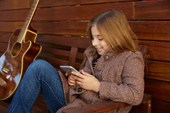 Blond kid girl playing smartphone Royalty Free Stock Photography