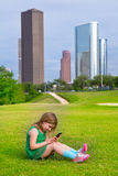 Blond kid girl playing with smartphone sitting on park lawn at c Royalty Free Stock Photography