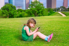 Blond kid girl playing with smartphone sitting on park lawn at c Royalty Free Stock Photos