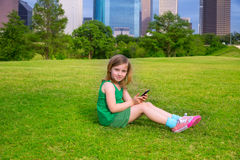 Blond kid girl playing with smartphone sitting on park lawn at c Royalty Free Stock Image