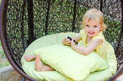 Blond kid girl playing with smartphone sitting in wicker chair Royalty Free Stock Images