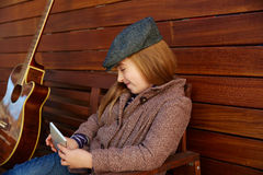 Blond kid girl playing smartphone winter beret Royalty Free Stock Photography