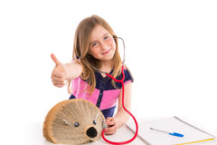 Blond kid girl pretending be doctor with hedgehog Stock Photos