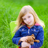 Blond kid girl with puppy pet dog in green grass. Blond kid girl with puppy pet dog sit in outdoor green grass royalty free stock photos