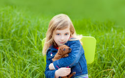 Blond kid girl with puppy pet dog in green grass. Blond kid girl with puppy pet dog sit in outdoor green grass royalty free stock images
