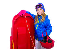 Blond kid girl with red sled snow equipment helmet and goggles Stock Photo