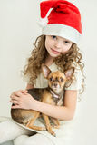 Blond kid girl in Santa Claus hat with small pet dog Royalty Free Stock Photos