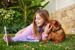 Blond kid girl selfie photo tablet pc and dog Stock Photo