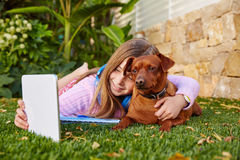 Blond kid girl selfie photo tablet pc and dog. Blond kid girl selfie photo with tablet pc and dog lying on grass royalty free stock photos