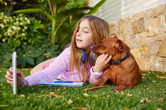 Blond kid girl selfie photo tablet pc and dog Royalty Free Stock Images