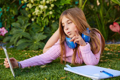 Blond kid girl selfie photo with tablet pc on grass Stock Image