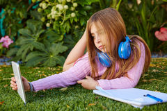 Blond kid girl selfie photo with tablet pc on grass Royalty Free Stock Photos
