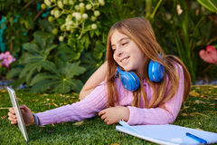 Blond kid girl selfie photo with tablet pc on grass Royalty Free Stock Images