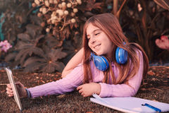 Blond kid girl selfie photo with tablet pc on grass Stock Photography