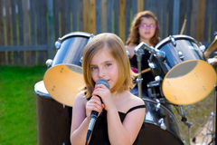 Blond kid girl singing in tha backyard with drums Royalty Free Stock Photos