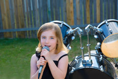 Blond kid girl singing in tha backyard with drums Royalty Free Stock Photography