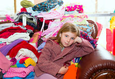 Blond kid girl sitting on a messy clothes sofa stock photo