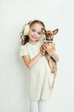 Blond kid girl with small pet dog. Russian toy stock photos