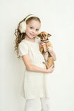 Blond kid girl with small pet dog Royalty Free Stock Images